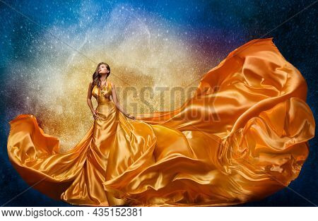 Fashion Model In Golden Dress Over Miracle Night Sky Background. Luxury Woman In Long Silk Gown Danc