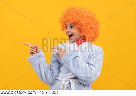 Happy Child In Fancy Orange Wig Hair Wear Home Bathrobe Pointing Finger On Copy Space, Advertisement