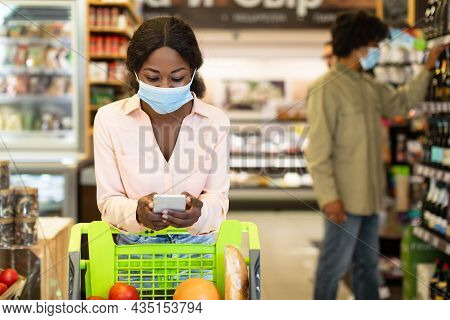 African American Woman Doing Grocery Shopping Using Smartphone In Supermarket