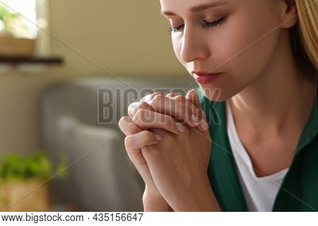 Religious Young Woman With Clasped Hands Praying Indoors, Closeup. Space For Text