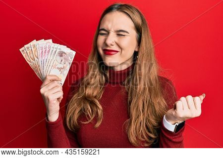 Young blonde woman holding turkish lira banknotes screaming proud, celebrating victory and success very excited with raised arm