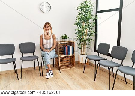Young caucasian injuried girl smiling happy wearing collar sitting at doctor waiting room.