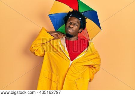 Young african american man wearing yellow raincoat suffering of neck ache injury, touching neck with hand, muscular pain