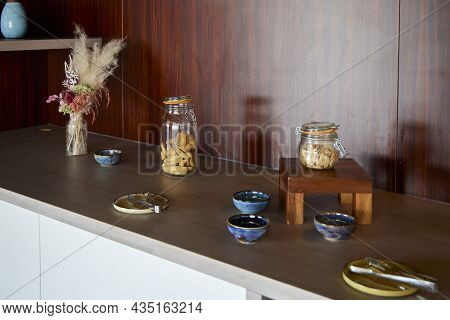 Glass Jar With Cookies. Placed On A Sideboard With Other Objects
