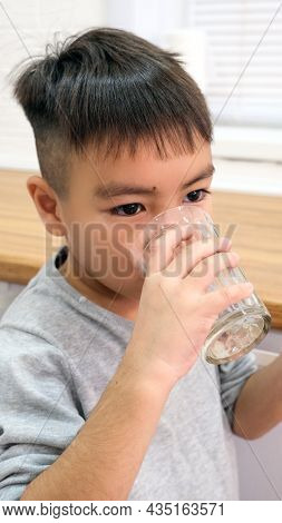 Close-up - A Little Boy Patient Swallows A Pill Of A Virus Capsule And Drinks A Glass Of Water After