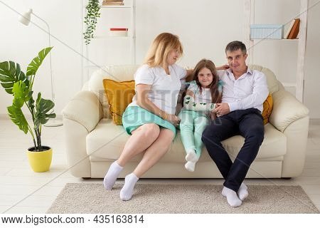Family Sitting On Sofa In Their Living Room. Daughter Have Injury Hand But She Is Happy Be Together