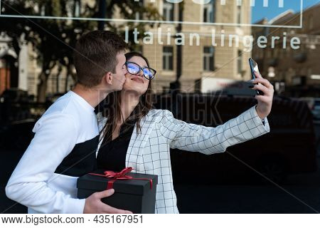 Young Couple In Love Makes Selfie With Gift In Their Hands. Guy Gives His Girlfriend A Gift And Kiss
