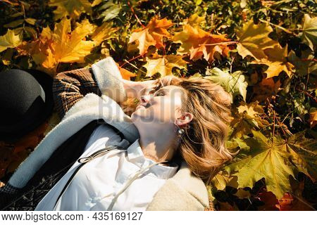 Carefree Young Woman With Curly Hair In Positive Mood Relaxing On Fallen Autumn Leaves, Smiling Girl