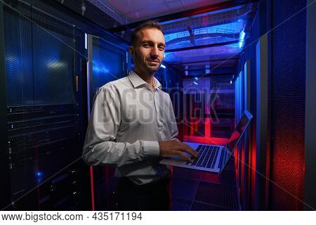 Bearded Smiling System Administrator Is Working With Server Rack And Telecommunication Equipments In