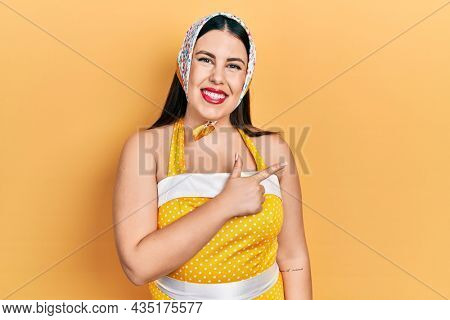 Young hispanic woman wearing pin up style smiling cheerful pointing with hand and finger up to the side