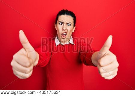 Young hispanic woman doing thumbs up positive gesture in shock face, looking skeptical and sarcastic, surprised with open mouth