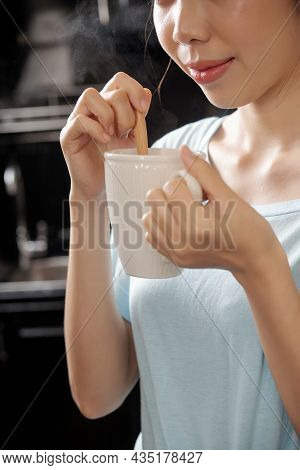 Close-up Of Content Asian Girl Stirrign Sugar With Spoon And Smelling Coffee Scent In Kitchen