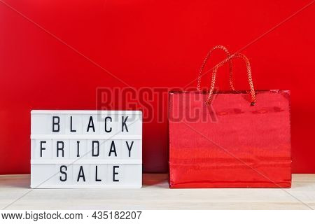 Black Friday Sale Concept. Gift Bag And Lightbox On A Red Background.