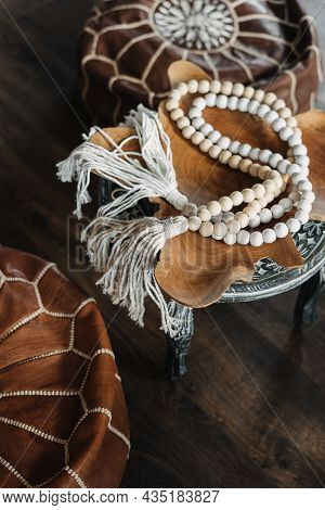 High Angle And Vertical View Of White Wooden Rosary Beads On Pouf With Ethnic Ornament. Home Decor A