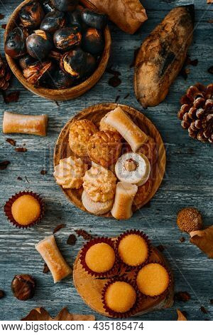 high angle view of a gray rustic table with some roasted chestnuts and some different confections eaten in Spain on All Saints Day, such as Panellets, Huesos de Santo or Yemas de Santa Teresa