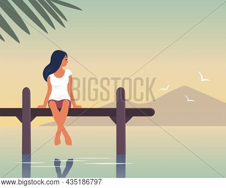 A Young Woman Is Resting By The Sea. A Girl Are Sitting On A Pier Above The Water. Happy Face With A