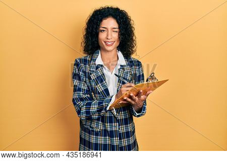 Young latin girl wearing business clothes writing on clipboard winking looking at the camera with sexy expression, cheerful and happy face.