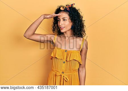 Young latin girl wearing summer dress very happy and smiling looking far away with hand over head. searching concept.