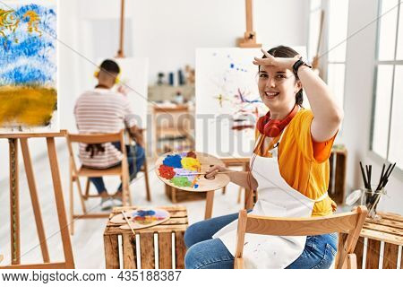 Young artist woman painting on canvas at art studio very happy and smiling looking far away with hand over head. searching concept.