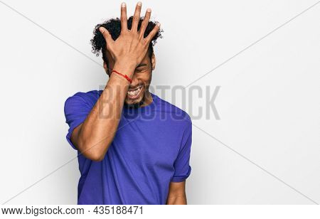 Young african american man with beard wearing casual purple t shirt surprised with hand on head for mistake, remember error. forgot, bad memory concept.