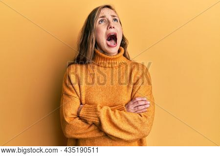 Young blonde woman with arms crossed gesture angry and mad screaming frustrated and furious, shouting with anger looking up.