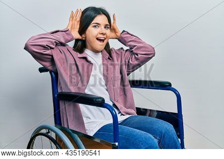 Young brunette woman sitting on wheelchair smiling cheerful playing peek a boo with hands showing face. surprised and exited