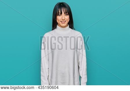 Young brunette woman with bangs wearing casual turtleneck sweater with a happy and cool smile on face. lucky person.