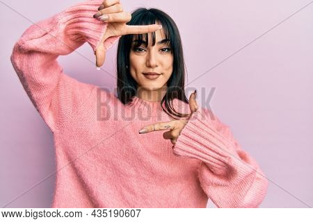 Young brunette woman with bangs wearing casual winter sweater smiling making frame with hands and fingers with happy face. creativity and photography concept.