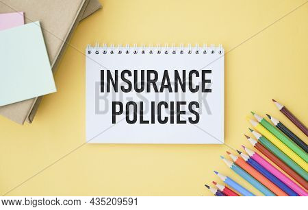 Insurance Policy Text In A Notebook On A Yellow Background With Colored Pencils.