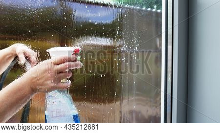 Window Cleaning With A Chemical Spray By Women From The Street Side, Glass Washer Visible Through Dr