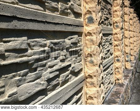 Stone Fence Made Of Light Material In A Linear Perspective, Embossed Exterior Wall Of Rounded Cobble