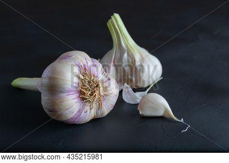 Two Garlic Heads And A Segment On Dark Background.