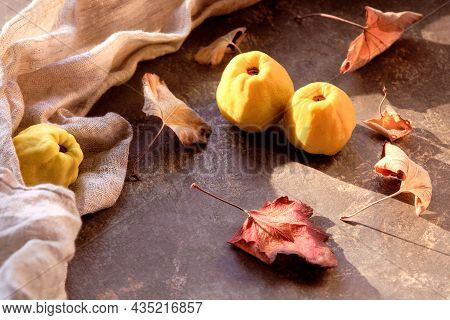 Close-up On Ripe Sweet Japanese Quince Fruits On Dack Table With Linen Towel And Dry Leaves. Autumn