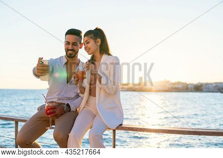 Cheerful Hispanic Loving Couple With Cocktails In Glasses Sitting On Railing On Promenade And Taking