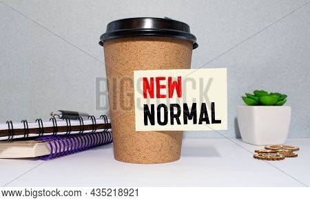 New Normal Inscription In A White Notebook Near A Cup Of Coffee On A Black Background