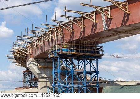 Construction Of An Automobile Steel Turning Overpass. Scaffolding And Crane At A Construction Site.