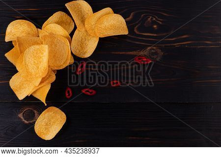 Potato Chips With Hot Peppers On Wood Background Top View With Copy Space.