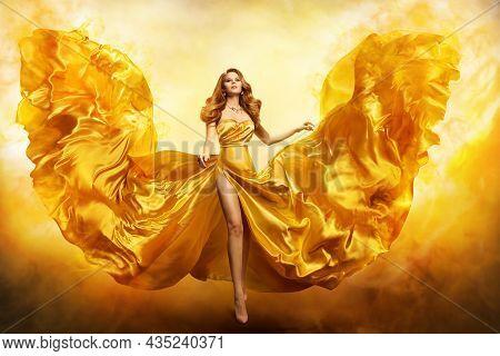 Fashion Woman In Yellow Gown. Fantasy Girl In Golden Dress Flying On Wind Like Phoenix Wings In Fire