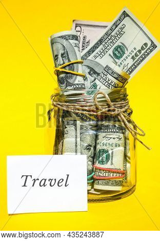 Glass Jars Filled With Dollar Bills, Savings Inside Glass Jar, Money Isolated On Yellow Background.
