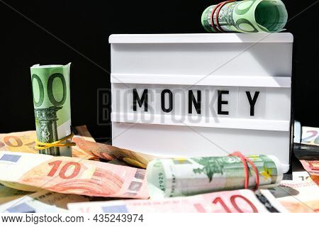 Lightbox Board With The Word Money In Black Letters Around Euro Banknotes. Finance Background. Busin