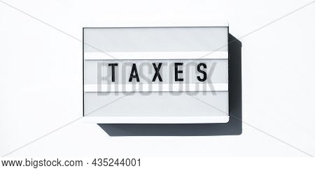 Lightbox Board On A White Background With The Words Taxes In Black Letters. Currency, Cash
