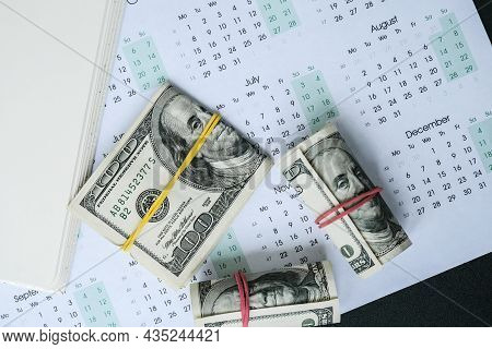 Office Workplace Desk With Dollars And Calendar. Counting Money For Salary. Investment Savings. Fina