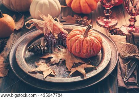 Place setting for Thanksgiving with pumpkins and autumn leaves in vintage style