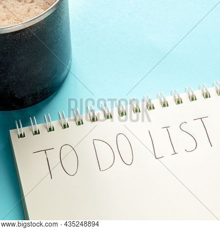 To Do List Square Shot With Handwriting In A Notepad And A Coffee Mug On A Blue Background. The Conc