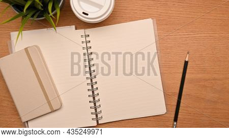 Top View Of Simple Study Desk With Blank Notebook Pages On Wooden Background