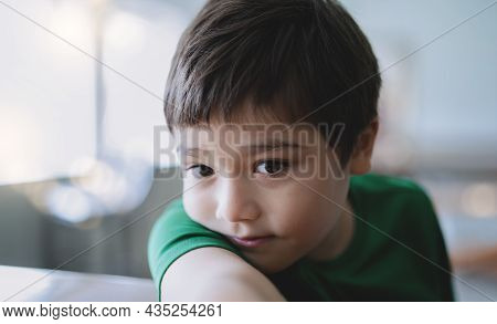 Close Up Face Of Cute Child Boy Lying Head On Arm, Candid Shot Young Kid Sitting Alone Looking Out D