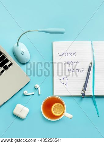 flatlay business, work from home, freelance, copywriting, top view laptop, notebook with work from home note and cup of tea on blue background.