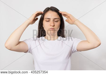 A 30-year-old Brunette Woman Holds Her Hands Near Her Temples On A White Background