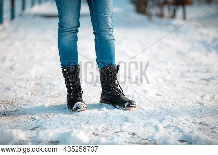 Female's Feet In Close-up, Wearing Boots With Anti-slip Protectors. Snow In The Background. Copy Spa
