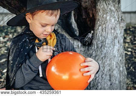 Halloween Kids. Cute Little Boy, Child In A Witch Hat Draws On An Orange Jack O Lantern Balloon. Hap
